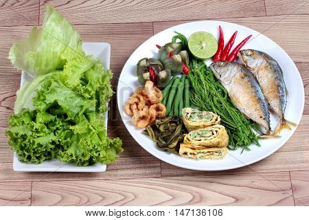 Ready side dish served as deep fired mackarelss,vegetable omelet,crispy pork rind,pickle lettuce,halve green lemon,red chili and boiled of eggplant,lentils,acacia  on wood. Side view