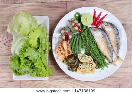 Ready side dish served as deep fired mackarelss,vegetable omelet,crispy pork rind,pickle lettuce,halve green lemon,red chili and boiled of eggplant,lentils,acacia on wood.Top view