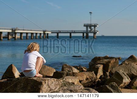 boy on the beach. he sits on the rocks. Bulgaria Burgas