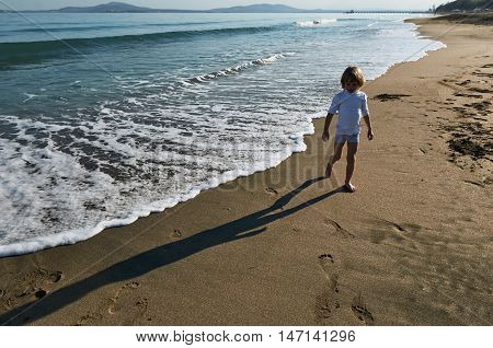 boy rejoice the sea. autumn outdoor. sunlight with shadow