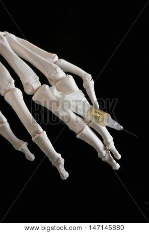 Drug abuse dangers - skeleton hand holding syringe with substance