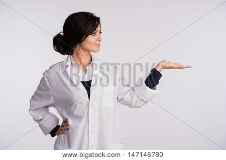 Pointing to blank copy space woman doctor nurse over white background.