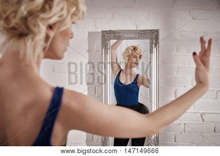Ballet dancer practicing front of mirror.