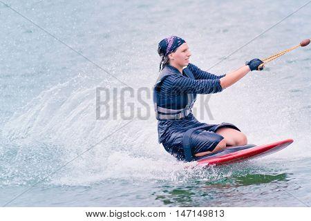 Young woman kneeboarding, toned image, horizontal image