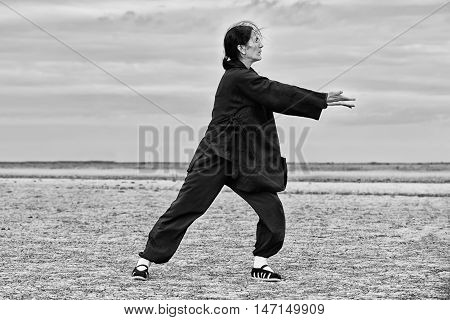 Woman practicing Qi Gong gathering energy, black and white image