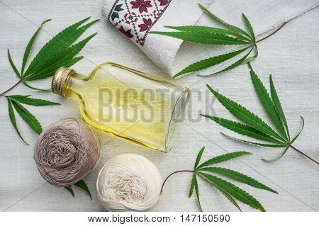leaves of cannabis, balls of yarn and bottle of hemp oil on canvas. Hemp products. Agricultural technical culture