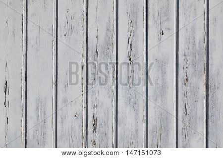 horizontal part of wooden fence or wall with old bladdered gray paint on planks