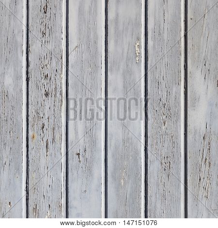 square part of wooden fence or wall with old bladdered gray paint on planks
