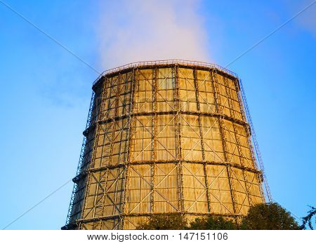 large thermal power station chimney at sunrise sunset with clear blue sky with the smoke from the chimney
