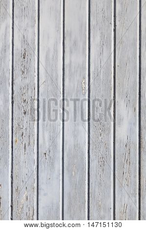 vertical part of wooden fence or wall with old bladdered gray paint on planks