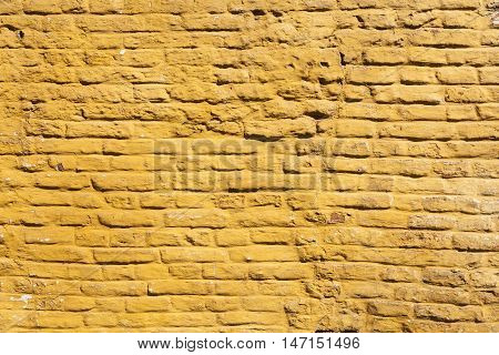 square part of ochre yellow painted brick wall