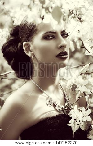 Black-and-white portrait of a beautiful brunette woman posing in the blossoming garden. Make-up, cosmetics. Medieval history, old times. Fashion. Gothic style.