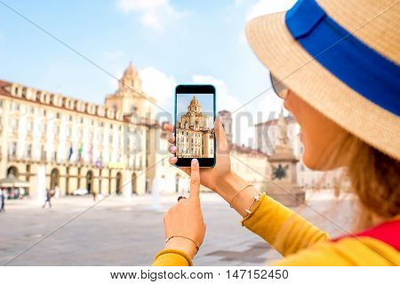Woman photographing with smartphone saint Lawrence church on the central square in Turin in Piedmont region in Italy
