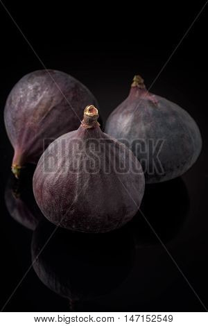 Balck figs isolated on black board and dark reflections