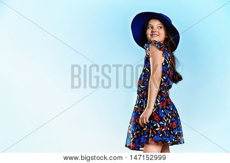 Happy eight year girl over blue sky on a bright sunny day. Summer holidays. Kid's fashion.