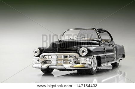The toy car on a gradient background. Car of black color. It is made of metal. A shadow and reflection from a surface. Indoors. Horizontal format. Photo.