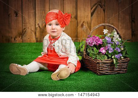Cute little baby girl on a green lawn over wooden background. Retro style. Summer.