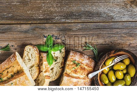 Green mediterranean olives in bowl and slices of freshly baked ciabatta over rustic wooden background. Top view, copy space, horizontal composition