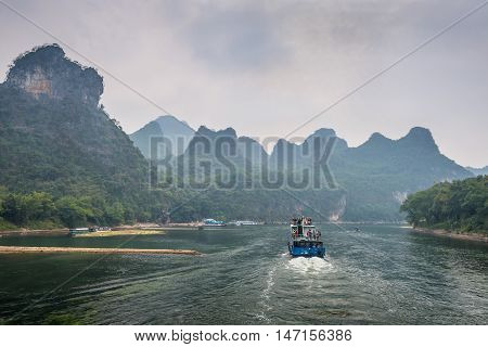 Xingping China - October 20 2013: A tourist boats travels the magnificent scenic route along the Li river from Guilin to Yangshou in cloudy weather.