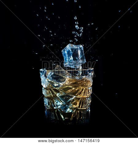 Whiskey With Ice Falling Into Glass Solated On Black