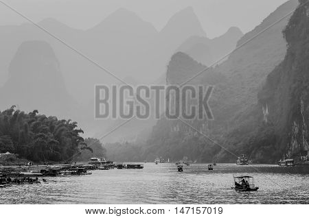Xingping China - October 20 2013: Cruise ship and boats packed with tourists travels the magnificent scenic route in the haze along the Li river from Guilin to Yangshou - black and white photography.