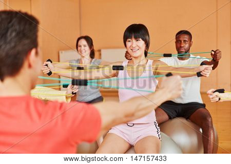 Interracial group with expanding bands during rehab class