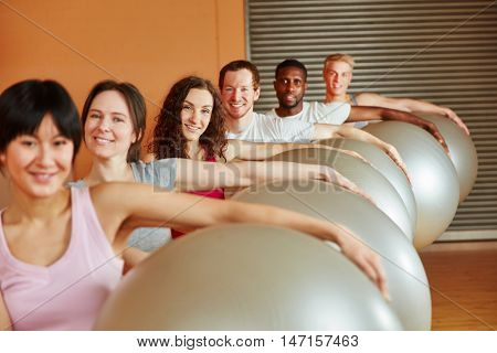 Interracial group with gym ball at the gym