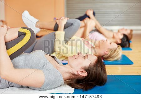 Woman and group of people making together gymnastics in pilates class
