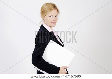 Young freckled businesswoman is standing self-confidently, looking into the camera with an elegance smile. Studio shot with light background. Isolated.