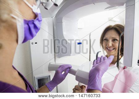 Dentist Gesturing Towards Smiling Patient Using Xray Machine