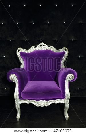Beautiful purple retro armchair in room with black soft wall