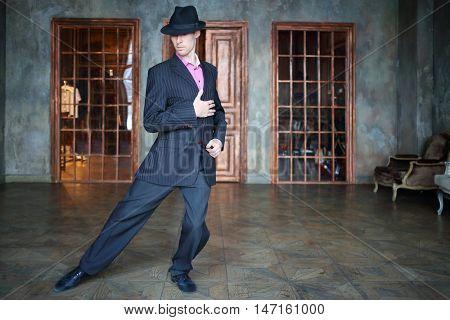 Man in suit dances tango in retro room with wooden doors and big windows