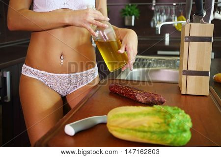 Woman in white underwear holds oil near table in kitchen, noface