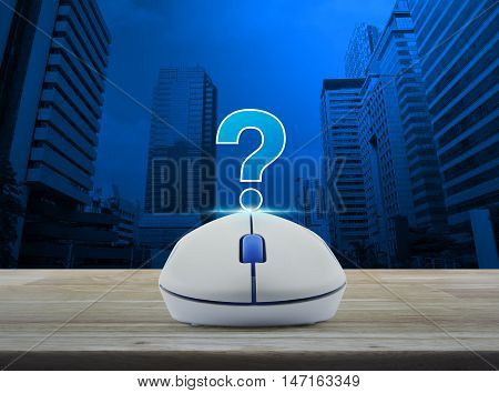 Wireless computer mouse with question mark sign icon on wooden table over city tower background Customer support concept