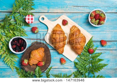Breakfast with croissants and strawberry on blue wooden table. View from above