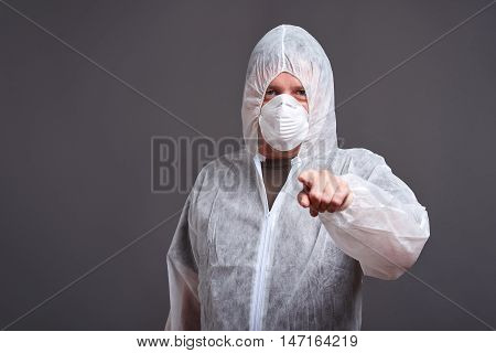 A middle aged man standing in a mask with the hoods on of the clothes protector suit and pointing to the camera
