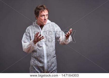 A middle aged man standing in a white clothes protector suit and feeling upset