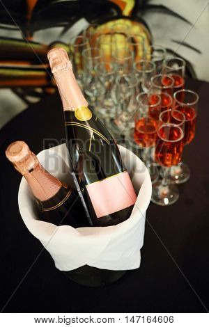 Glasses with Sparkling rose wine and two bottles in ice bucket