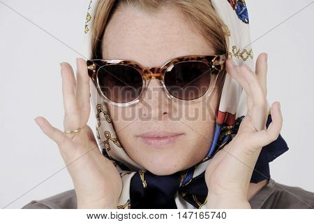 Young woman is wearing scarf and sunglasses in a Grace Kelly Style. Studio shot with light background. Isolated.