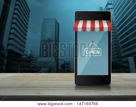 Modern smart mobile phone with on line shopping store graphic and open sign on wooden table over city tower background