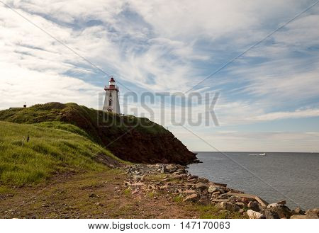 Lighthouse on rocky shores of Prince Edward Island, Canada with cloudy blue skies.