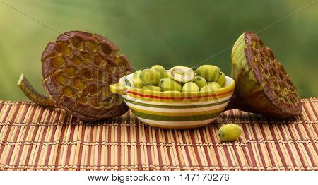 Fresh green lotus seed (lotus nut) in ceramic bowl and two lotus seed boxes on green background