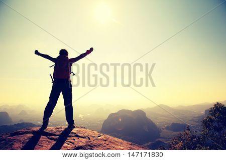 cheering woman hiker at sunrise mountain peak