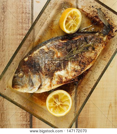 Delicious Homemade Roasted Sea Bream Fish with Lemons and Rosemary in Glass Cooking Tray closeup on Wooden background. Top View