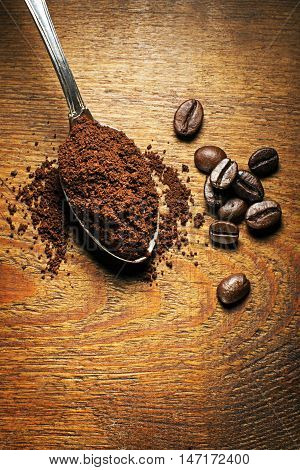 Fresh ground Coffee in spoon on wooden background