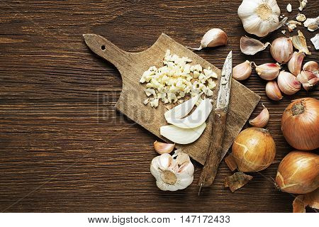 Garlic cloves and onions on wooden vintage background