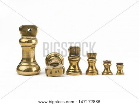 A set of antiques brass imperial weights isolated on a white background. showing 4oz
