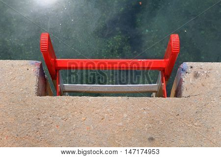 Bright Red Metal Ladder On A Concrete Quayside Leading Down To The Clear Green Water Of A Harbour, W