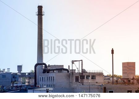 Factory with big chimney on the early morning with a clear sky