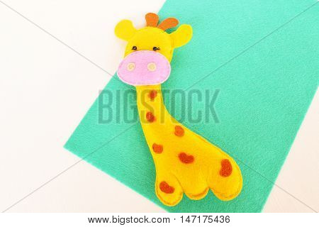 Funny felt giraffe on blue background. How to sew felt yellow giraffe. Soft toy for children. Step